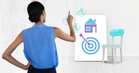 Digital composite of Woman pointing with business icons on white board