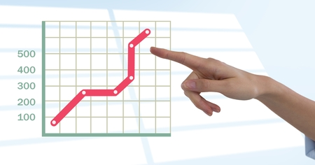 Digital composite of Hand pointing with grid chart statistics