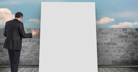 Digital composite of Businessman standing by white board