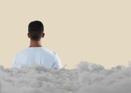 Digital composite of Teenager looking forward with clouds behind him Stock Photo