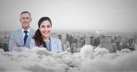 Digital composite of Business man and woman facing out with city skyline behind them and clouds in front Stock Photo