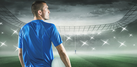 Rugby player looking away while holding ball against rugby stadium