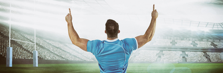 Rugby player cheering and pointing against rugby pitch Stock Photo