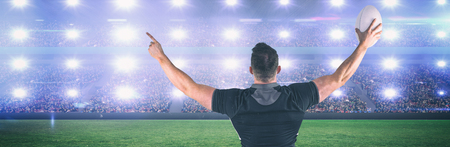 Rugby player celebrating with the ball against digital image of crowded soccer stadium Stock Photo
