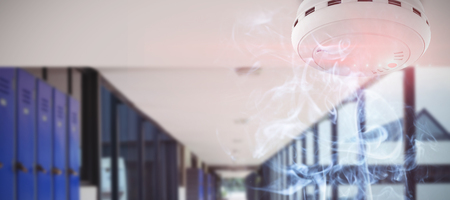 Fire and smoke detector against empty corridor at school