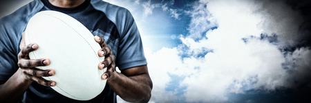 Mid section of sportsman holding rugby ball against spotlight in sky