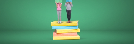 Digital composite of Two girls reading and standing on a pile of books with green background Stock Photo