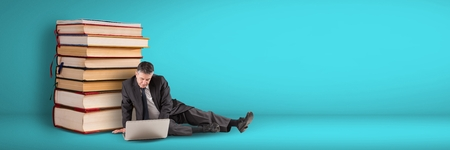 Digital composite of Business man using computer on the floor next to a pile of books on blue background
