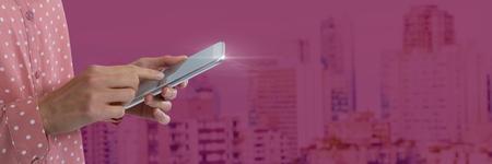 Digital composite of Hand holding tablet pink background