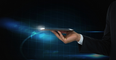 Digital composite of Hand holding tablet with blue technology background
