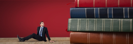 Digital composite of Business man looking up and sitting next to a pile of books