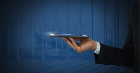 Digital composite of Hand holding tablet with dark background Stock Photo