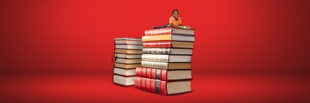Digital composite of Boy reading on a pile of books with red background