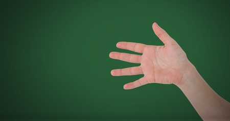 Digital composite of Hand open with fingers on green background