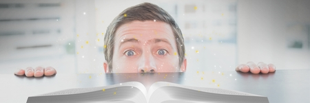 Digital composite of Man looking at an opened book with lights on a table
