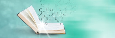 Digital composite of Opened book with light and letters on green background