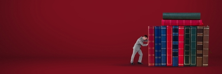 Digital composite of Businessman pushing books on red background