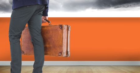 Digital composite of Businessman with briefcase and orange wall