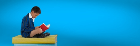 Digital composite of Boy reading and sitting on a pile of books with blue background