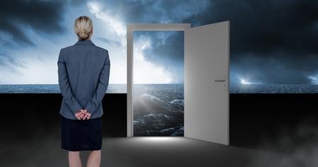 Digital composite of Businesswoman standing by open door with surreal dark sea glow and sky Foto de archivo - 96578869