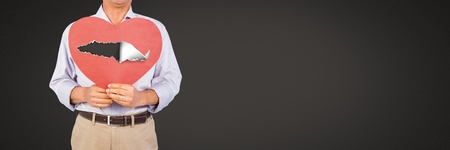 Digital composite of Man holding hurt love heart with torn paper