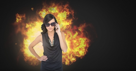 Digital composite of Cool sexy woman in sunglasses with burning fire flames