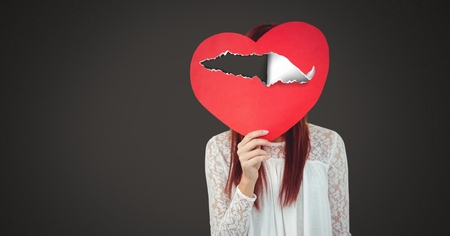 Digital composite of Woman holding hurt love heart with torn paper