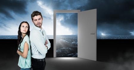 Digital composite of Couple standing by open door with surreal dark sea glow and sky