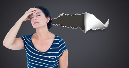 Digital composite of Stressed and upset woman with torn paper Фото со стока
