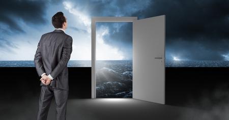Digital composite of Businessman standing by open door with surreal dark sea glow and sky Reklamní fotografie