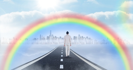 Digital composite of Businesswoman walking on road with surreal time clocks perspective and rainbow