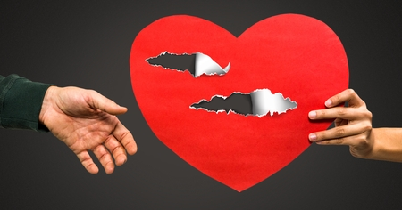 Digital composite of Couple holding hurt love heart with torn paper