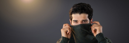 Digital composite of Man hiding under jumper with eyes peering out
