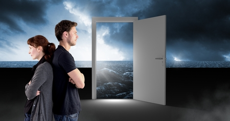 Digital composite of Couple standing by open door with surreal dark sea glow and sky