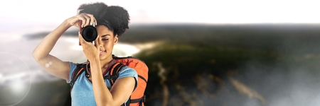 Digital composite of Travelling woman with bag and camera in front of landscape Stok Fotoğraf