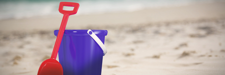 Blue bucket and red shovel against piggy bank with sunglasses kept on sand Stock Photo
