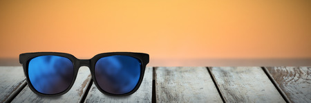 Close-up of sunglasses against waves crashing at sunset Stock Photo
