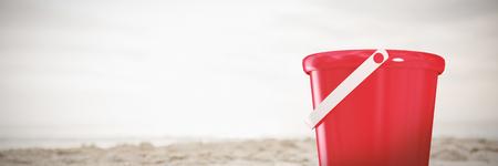 New red bucket against orange flip flop in sand