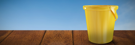 New yellow bucket against beautiful sunset on a sunny day Stock Photo