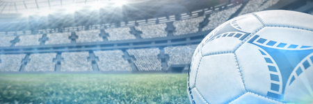 Soccer ball on white marking line against view of a stadium Stock Photo