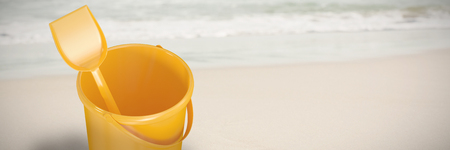 Yellow bucket and shovel against piggy bank with sunglasses on sand shore
