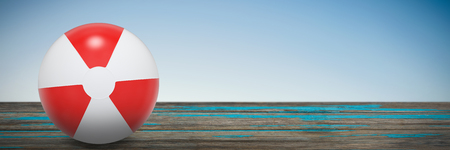 Red and white ball against scenic view of beach Stock Photo