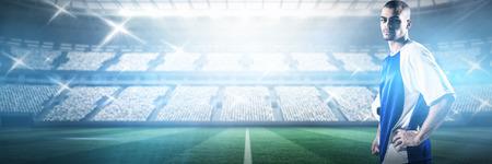Portrait of confident player holding football against stadium against sky