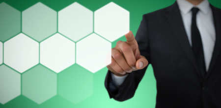 Mid section of businessman with pointing gesture against abstract green background