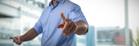 Male executive pressing an invisible virtual screen while using mobile phone against working desk in a office
