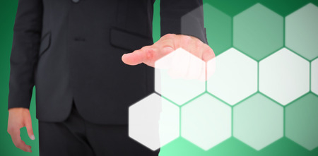 Businessman pointing with finger against abstract green background