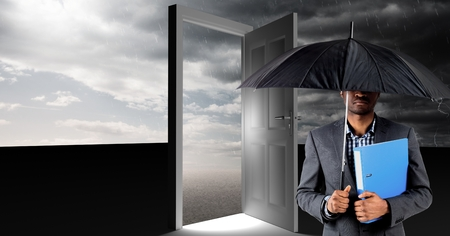 Digital composite of man holding umbrella and surreal open door with grey cloudy sky Stock Photo