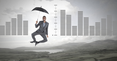 Digital composite of man floating with umbrella and bar charts over nature landscape