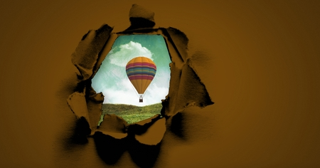 Digital composite of Hot air balloon floating through surreal paper hole Stock Photo