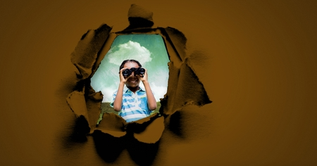 Digital composite of child looking through binoculars in surreal hole in paper